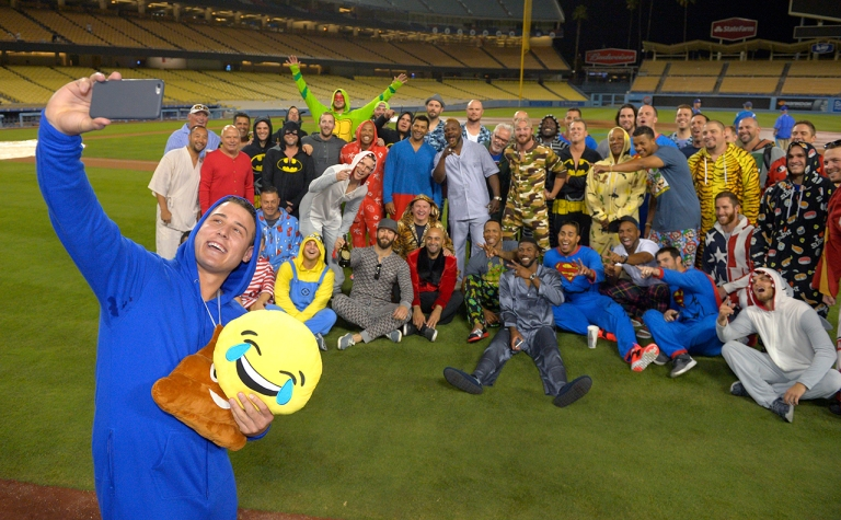 Chicago Cubs first baseman Anthony Rizzo, left, takes a photo as teammates pose in the background following a baseball game against the Los Angeles Dodgers, Sunday, Aug. 30, 2015, in Los Angeles. The players are wearing pajamas for an overnight flight to Chicago after finishing a six-game West Coast trip. The Cubs won 2-0 after Jake Arrieta pitched his first career no-hitter. (AP Photo/Mark J. Terrill)
